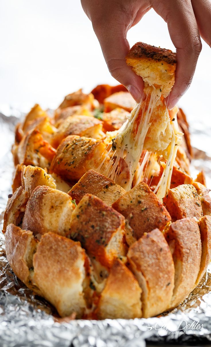 This Garlic Butter Pizza Pull Apart Bread is smothered in garlic butter, stuffed with pizza fillings, and topped with so.much.cheese!