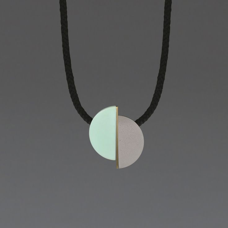 Klee Necklace: Offset resin semicircles separated by a brass bar. Black cord full drop 45cm. Necklace is adjustable at the back with a small wooden ball meaning it can be worn short or at pendant length to suit any neckline.  Comes packaged in a beautiful kraft tube.  one we made earlier make contemporary accessories.  Based in London, husband and wife team Emma and Rob Orchardson draw on their backgrounds in fine art and design to create bold statement pieces.  Their work combines a playful…