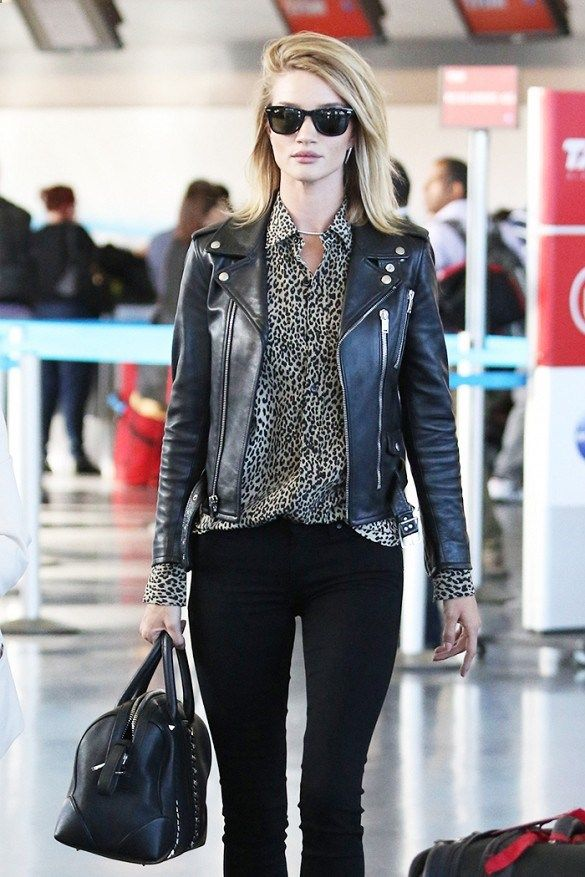 Rosie Huntington-Whiteley wears a leopard print button-down shirt, leather motorcycle jacket, skinny jeans, Ray-Ban wayfarers, and a black leather duffle purse