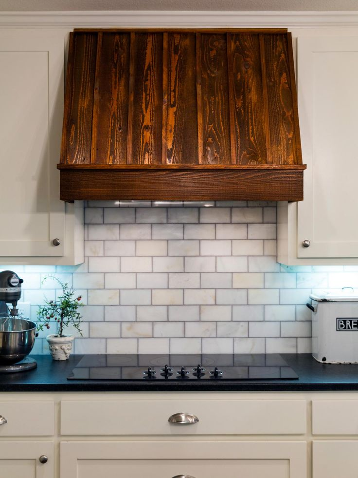 Designers Chip and Joanna Gaines marry new technology with old-world style in this kitchen, which features a glass electric stove top and wooden range hood.
