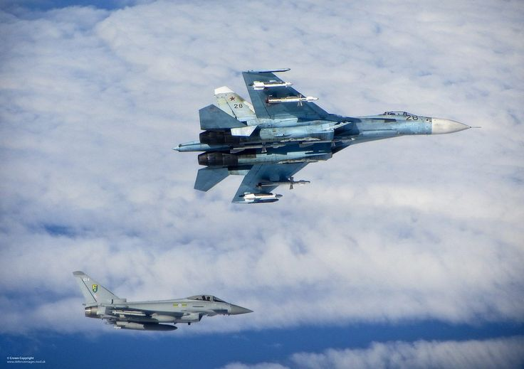 A Russian SU-27 Flanker aircraft banks away with a Royal Air Force Eurofighter Typhoon in the background. (Defence Images/Flickr) #armedforces #aircaft #airforce#aviation #aviationgeek #avgeek...