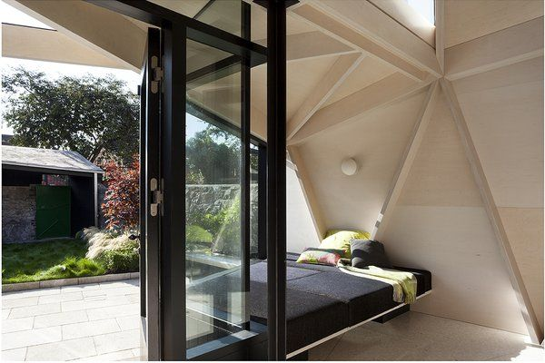 A custom OIKOS Furniture window seat is nestled between the extension's large windows and its latticework structure. Built out of glue-laminated plywood beams, the extension's diagonal grid provides structural support and visual interest.