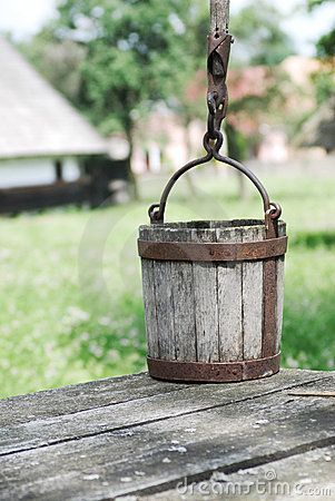 Old wooden water bucket, outside photograph with rural background. Not a firkin, but a wooden bucket.