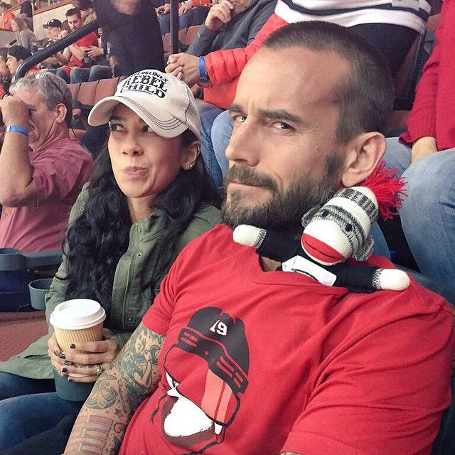 Former WWE Superstar CM Punk (Phil Brooks) and his wife, former WWE Diva AJ Lee at a NHL Chicago Blackhawks game