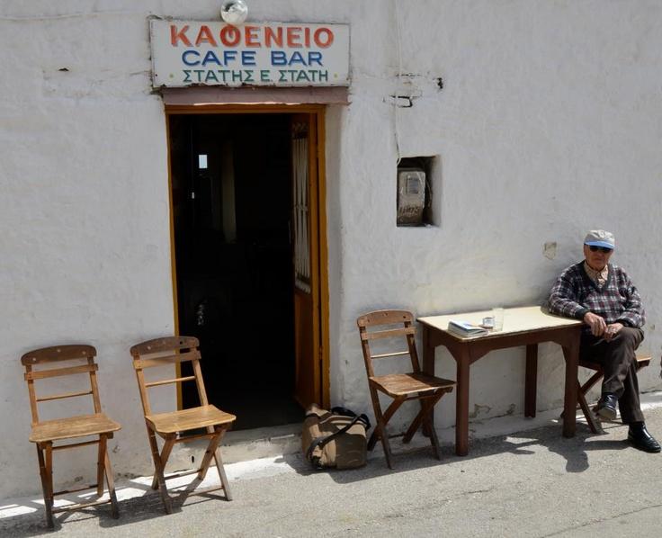 """Ο καφενές του Στάτη (Ευστάθιος) Στάτη στον Αγιο Ισίδωρο. Οι περαστικοί κάθονται στις χαρακτηριστικές ροδίτικες καρέκλες πάνω στη δημοσιά. Αυτοκίνητα περνούν ελάχιστα και έτσι δεν υπάρχει κανένας κίνδυνος. Ο καφετζής 85 χρονών όταν ρωτήθηκε για τον λόγο που βαστά ακόμα-60 χρόνια τώρα-το μαγαζί: """"Γιά να γειτονεύω γιόκα μου""""."""