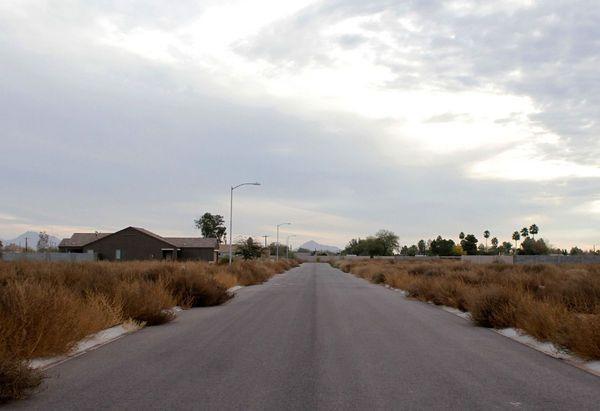 Асфальтированная дорога в окружении сорняков. Фото сделано в недостроенном в результате кризиса поселении Кулидж, Аризона, США.