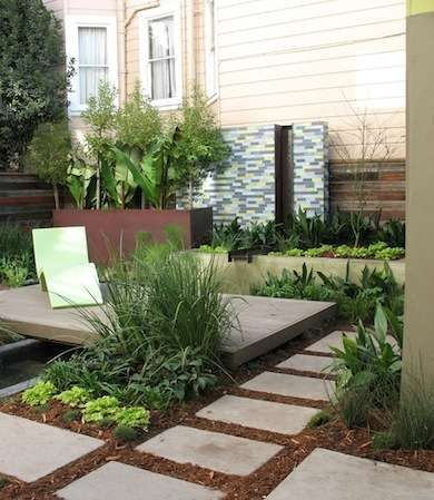 Many small and urban lawns can be replaced with hardscapes that provide relaxation and entertainment spaces just as enjoyable as a traditional grass yard. This patio is surrounded by container gardens and a flagstone walkway lined with lush plantings that serve up plenty of green garden pleasure.