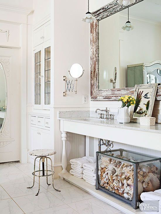 A vintage milking stool and seashell-stuffed aquarium highlight this bathroom's mix of country and cottage styles. To get a similar look, start with a white backdrop that will show off chipped patinas and beachcombed treasures. Install vintage-looking light fixtures, faucets, mirrors, and hardware to instill an aged appearance. /