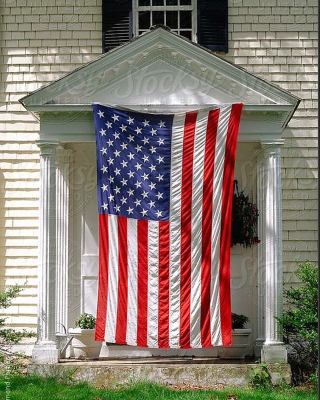 The American flag is the most recognized symbol of freedom and democracy in the world.  This #stockphoto is available via Stocksy United Search: #raymondforbesllc #america #american #americanflag #architecture #patriotic #display #unitedstatesofamerica #hangingholiday #home