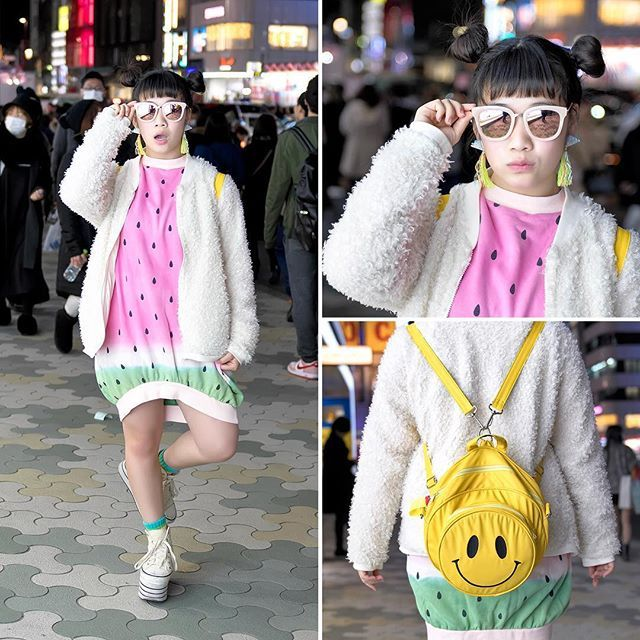 Karin (@karin.tempurakidz) from the Japanese dance group Tempura Kidz on the street in Harajuku wearing a watermelon print dress and smiley face backpack (both from Candy Stripper) with a resale fuzzy sweater, platform sneakers, and Vannie Tokyo accessories.