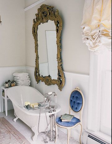 Traditionally inspired bathroom featuring a roll top bath, large mirror and wooden shelving