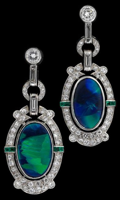 Art Deco platinum, opal and diamond earrings Oval black opal in petite round cut diamond surround, accented by petite caliber cut emeralds; post backing.