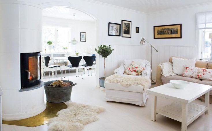 Kakelugnen från Jötul sprider skön värme i stora rummet. Soffa från Mio. Soffbordet har familjen byggt av husets gamla ytterdörr.  En röd tråd har funnits med under hela renoveringsresan: all fast inredning som till exempel inbyggda hyllor ska se ut som den alltid har funnits i huset och alla snickerier, både in- och utvändigt, ska vara vita.