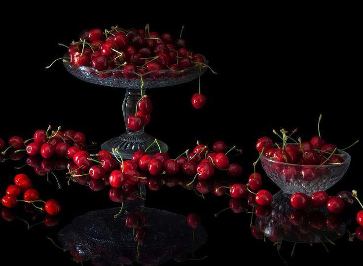 Обои для рабочего стола Ягоды вишни в вазах и на столе с зеркальной поверхностью на черном фоне