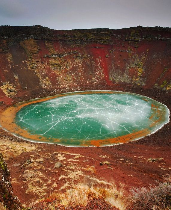 Kerið, Iceland While many crater lakes are deep within black volcanic rock, the rock around the colorful Kerið Lake in Iceland is a mix of red, brown, and pink. The 3,000-year-old crater sits within the tourist route known as the Golden Circle. #iceland #volcano #fireandice