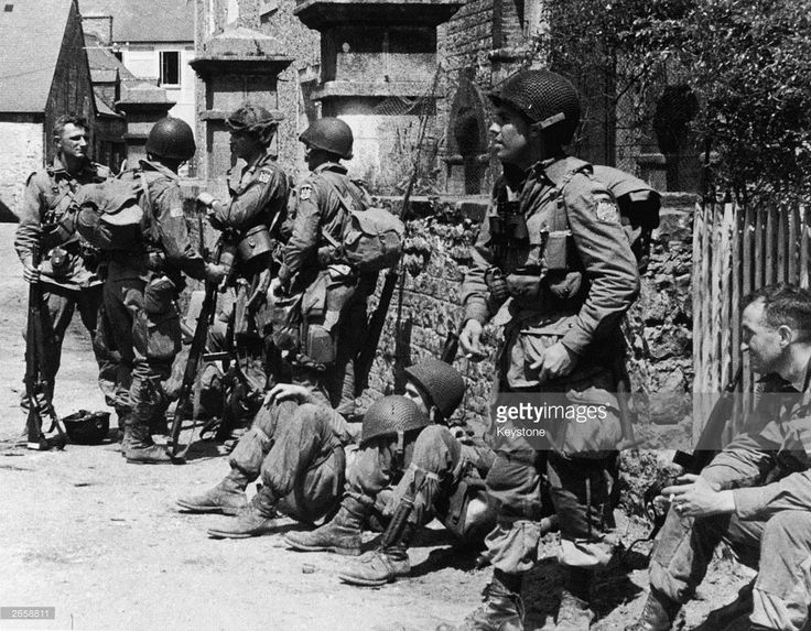 US paratroopers of the 82nd Airborne Division relaxing after liberating the village of Sainte-Mere-Eglise in Normandy, 8th June 1944. The shoulder patch of the nearest standing soldier has been erased, presumably by the censors.