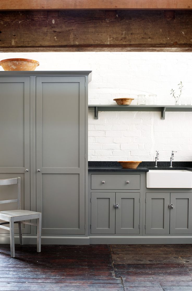 Distressed + varnished wood floor, gray painted cabinets, white walls