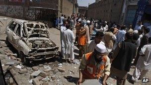 People gather at the site of an explosion outside an election office of a candidate in Peshawar, Pakistan, 28 April 28, 2013