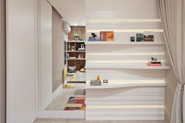 Silvana Andrade arquitetura - A parede em frente à mesa recebeu um espelho + um painel/estante em laca branca com iluminação de led.