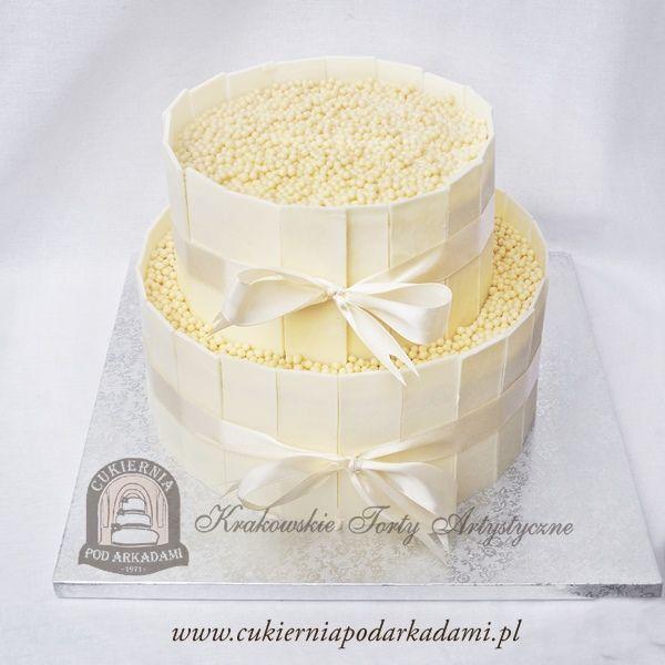 6BW Tort weselny piętrowy z tabliczkami białej czekolady i kuleczkami ryżowymi. Dekoracja z delikatnej satynowej wstążki. Wedding cake with white chocolate and rice balls.