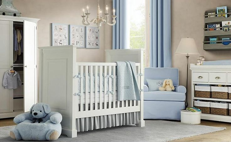 Subtle light blue curtains, armchair, and bedding complement light beige walls and white painted furniture in this nursery, with light rug over hardwood floor.