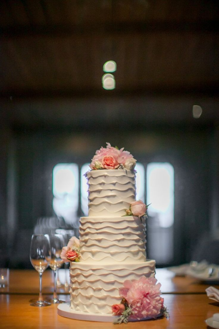 Elegant white ruffled three-tier wedding cake with pink flowers (Clane Gessel Photography)