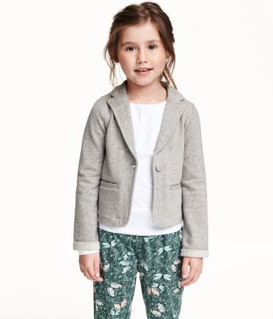 Jacket in light sweatshirt fabric containing glittery threads with a collar and lapels, front pockets and sewn-in turn-ups at the cuffs. Unlined.