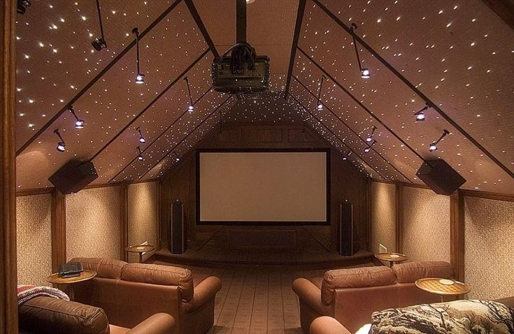 This home theater puts a converted attic to perfect use with a suspended projector, cushy loveseats, and lighting that evokes a starry night sky.