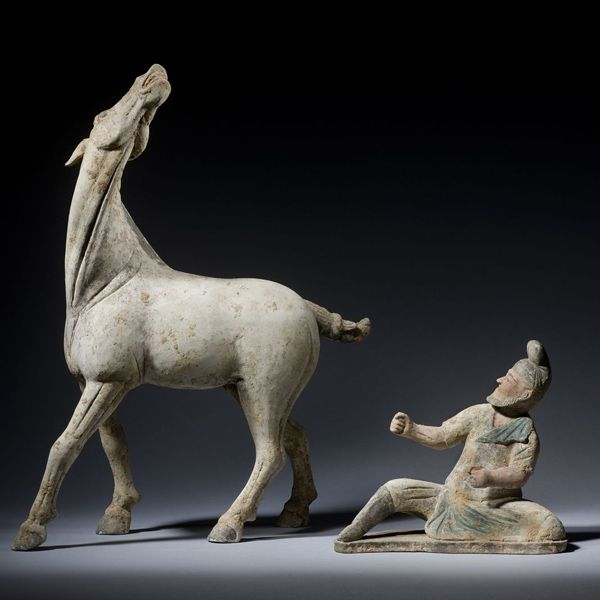 Mozo de caballos (caballerizo) atiende a un caballo. A&J Speelman Oriental Art | Chinese | Early Ceramics | An unglazed terracotta horse with raised neck and head, together with a seated foreign groom