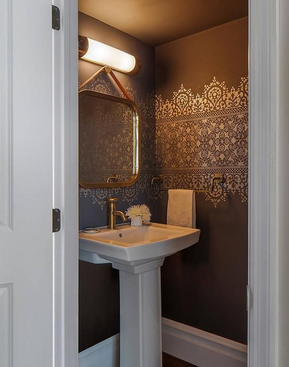 Gold and brown powder room features walls painted chocolate brown accented with gold stencils lined with a pedestal sink and a gold mirror hanging by a leather strap.