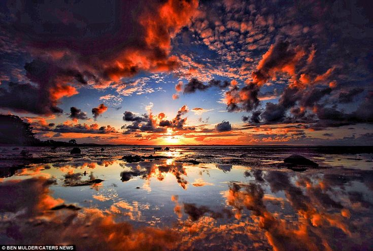 This stunning image shows vivid reds, blues and oranges in the cloud lining and reflected ...