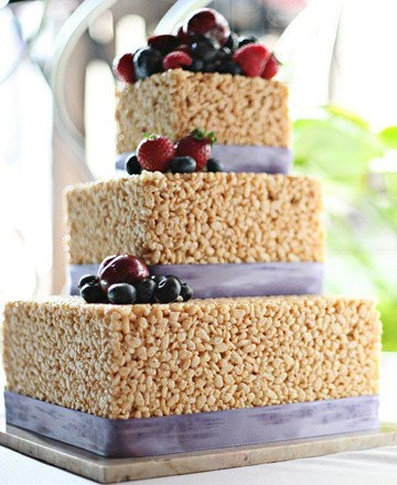 A fun alternative to a traditional wedding cake! This Rice Krispie Treat wedding cake is one-of-a-kind, but beautifully decorated with ribbon and delicious fruit. We have seen so many treat-inspired wedding cakes such as Oreos, macaroons and cake-pops. All of these delicious treats are some how made into tiers to resemble a wedding cake with a sweet twist!