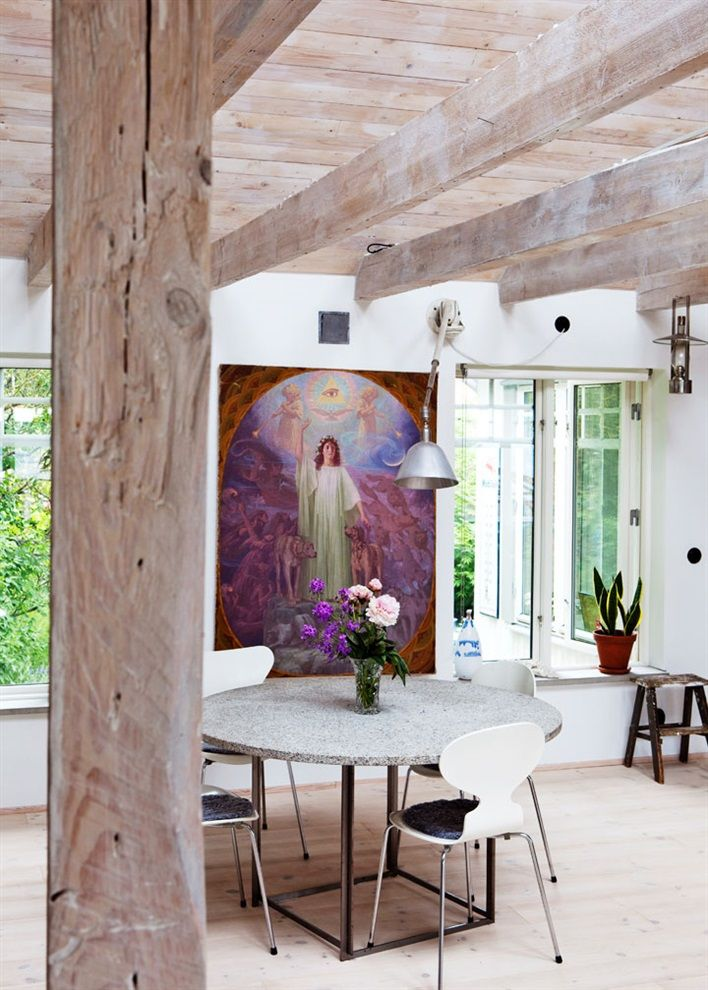 Dining table in wooden ceiling and interesting purple painting with flower to match.