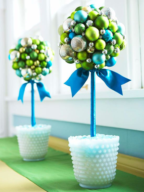 Glass Ball Topiaries  A colorful mix of vintage and new glass ball ornaments covering foam balls supported by ribbon-wrapped dowels form festive topiaries. Milk-glass vases add vintage charm.