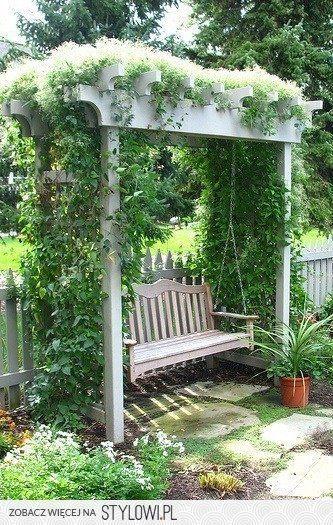 Romantische Schaukelbank im Garten unter zugewachsener Pergola