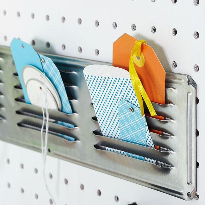 Turn an aluminum under-eave vent into a storage solution. Hold it in place on pegboard using twist ties or cable ties. Gift tags of all shapes and sizes fit nicely into the slots.
