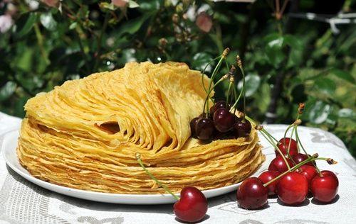 Обои Стопка блинов лежащая на белой тарелке с ягодами черешни и вишни