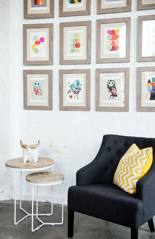 Confident and cheeky: Brightly coloured, vintage inspired prints and mango wood side tables. Charcoal grey plaid, buttoned occasional chair and citrus yellow chevron cushion.