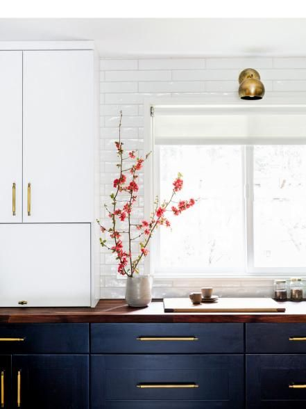 Designer Kenna Stout transformed this once confining galley-style kitchen into a vibrant, open-concept design. Where smooth subway tile and black cabinets keep the space modern, woven area rugs and brass hardware infuse it with warmth and color.