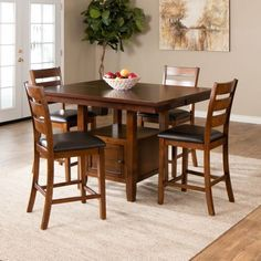 The Taylor counter height set offers fine craftsmanship & style, featured in a warm brown finish on solid hardwood and veneers. The table has a butterfly leaf extending the table to accommodate extra guests and a storage base with 2 doors. The chairs have a triple slat back with faux leather ...