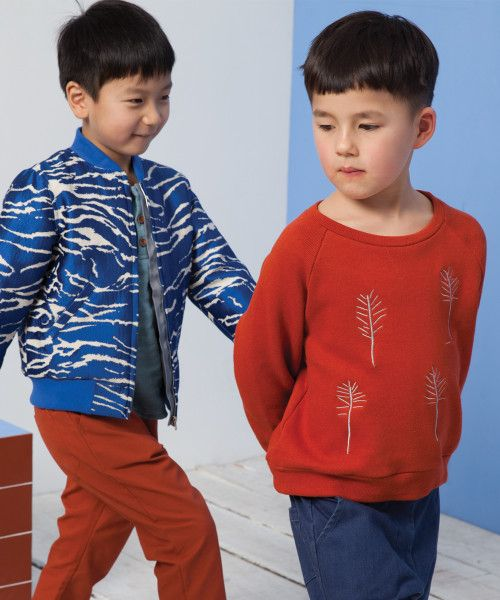 Rust embroidered tree sweatshirt and electric blue jacquard zebra bomber. Milk & Biscuits