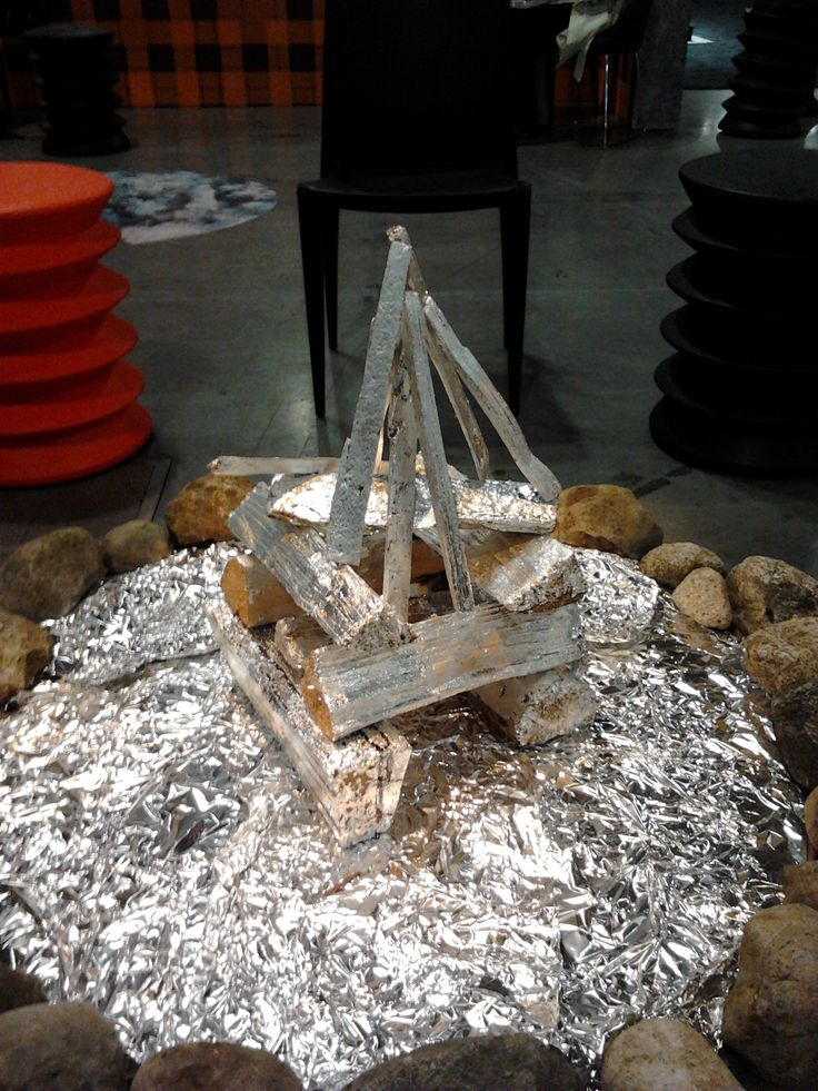Fire's burning...NOT. Circle of rocks with aluminum foil, silver painted logs, spinning light overhead to give illusion of flickering flames. Sorry... this just did NOT work for me. (I'm spoiled by the REAL thing.)