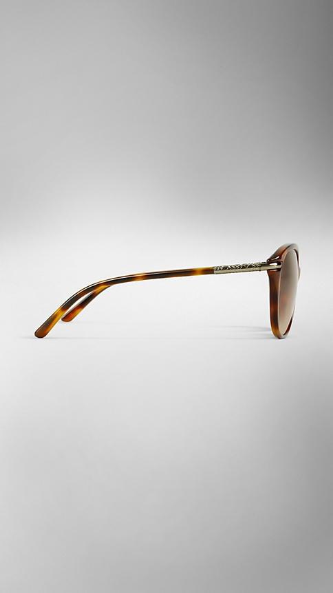 Occhiali da sole in acetato guscio di tartaruga con elegante montatura occhi di gatto  Stanghette tubolari e dettaglio in metallo color oro chiaro con motivo check inciso  Lenti antigraffio marrone sfumato  100% protezione UV