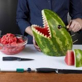 hands carving watermelon to look like a shark