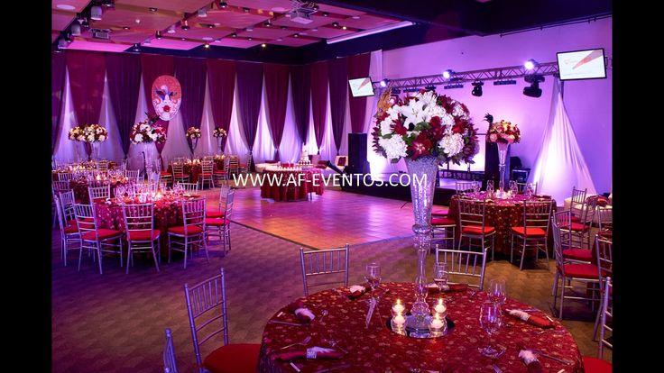 Vista completa del salón y la decoración, con la miniTK y pista de baile donde se aprecian los centros de mesa altos y las máscaras venecianas de 2 mts colgadas del techo.  @afeventos
