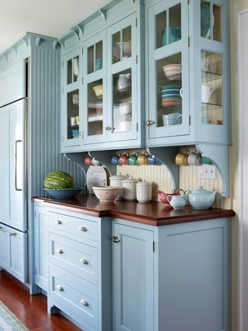Blue cabinets are an unusual choice, but the effect is pure charm. Off-white beaded-board walls, hardwood countertops, and vintage-inspired cabinet hardware create a bright, beautiful space that connotes a cottage look in this kitchen.