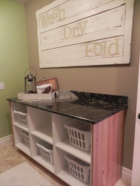 Love the laundry room art.  And a laundry folding table with basket storage for each person in the house?  Be still my heart.
