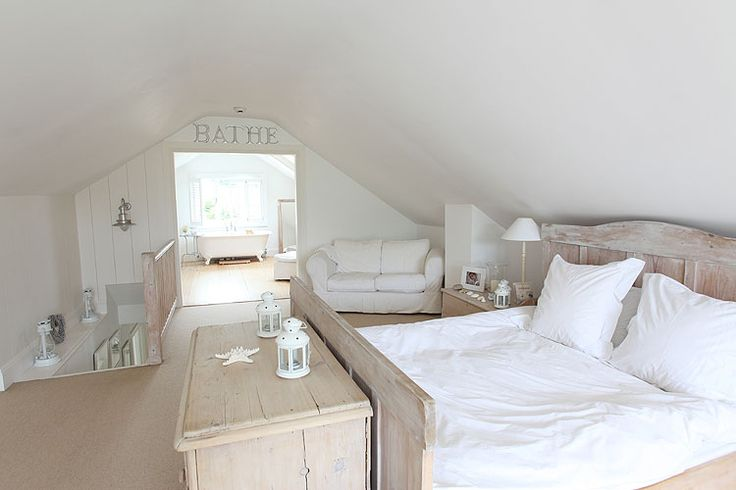 White attic room with bleached wood furniture, white linens and free standing bath  Forehead Kisses