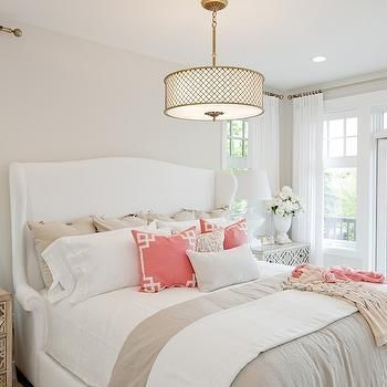 White Wingback Bed in this luxe bedroom decorated with tan on white and a splash of coral.