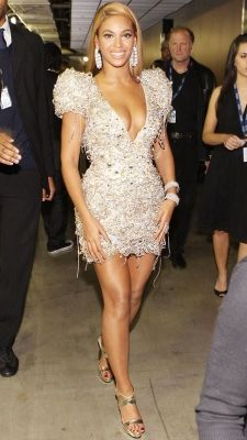 """Stylish dresses made unforgettable by the famous. (MSN.com) 2010: Beyonce in Armani Prive.  """"Shoulder pads make a comeback. And nothing says """"outta-my-way"""" like a couture version large enough for a linebacker, when rendered in crystal-covered chain metal.""""  MSN says it all for me, so I can just continue laughing.  What are those strings hanging down from the hem?"""